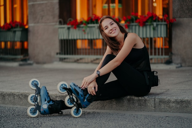Pleasant looking young european woman wears rollerskates takes break after riding poses outdoor dressed in black activewear has happy smile on face. people recreation hobby and lifestyle concept