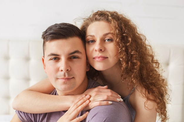 Pleasant looking young female hugs her handsome boyfriend, pose together against domestic interior, spend day off at home