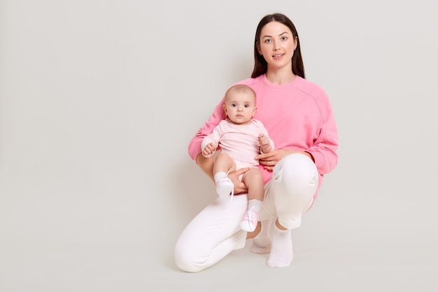 Pleasant looking young female wearing casual attire squats with baby girl on leg and looking directly at camera, attractive mother with her daughter isolated over white wall.