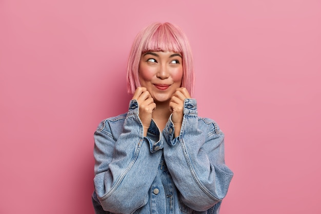 La ragazza dall'aspetto piacevole guarda con un'espressione sognante, indossa una parrucca di capelli rosei, sorride felice