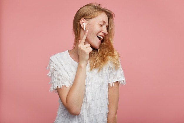 Pleasant looking young glad redhead female dressed in white festive t-shirt smiling cheerfully while listening to music with closed eyes, standing against pink background