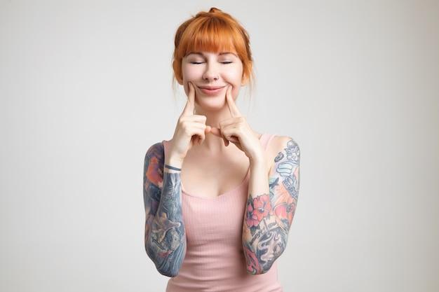 白い背景の上に立って、元気に笑っている間彼女の目を閉じたままにしてカジュアルな髪型で快適に見える若い嬉しい赤毛の入れ墨の女性