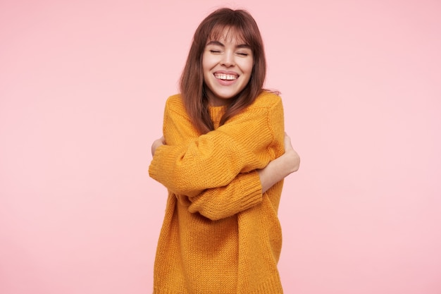 겨자 모직 스웨터를 입고 즐거운 찾고 젊은 행복 갈색 머리 여자는 사랑스럽게 자신을 포옹하고 눈을 감고, 분홍색 벽 위에 서서