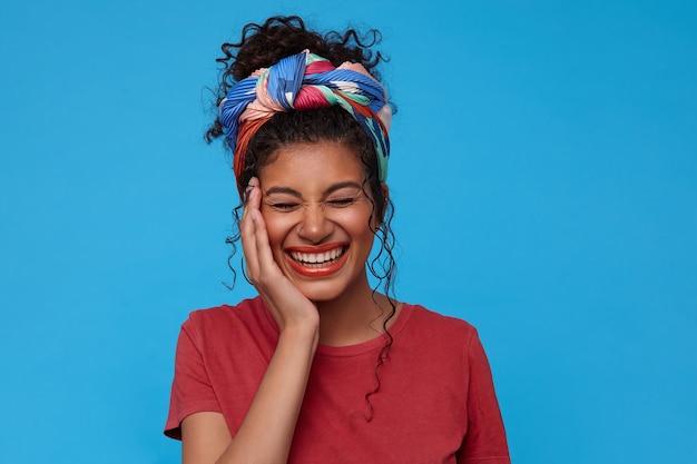 青い壁に隔離された彼女の頬に上げられた手のひらを持って元気に笑っている間彼女の目を閉じたままにして快適に見える若い幸せな黒髪の巻き毛の女性