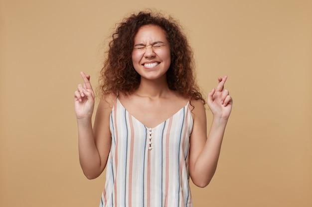 Piacevole giovane bella donna dai capelli castani ricci mantenendo le mani incrociate mentre esprime desiderio e incrocio le dita per buona fortuna, isolato su beige