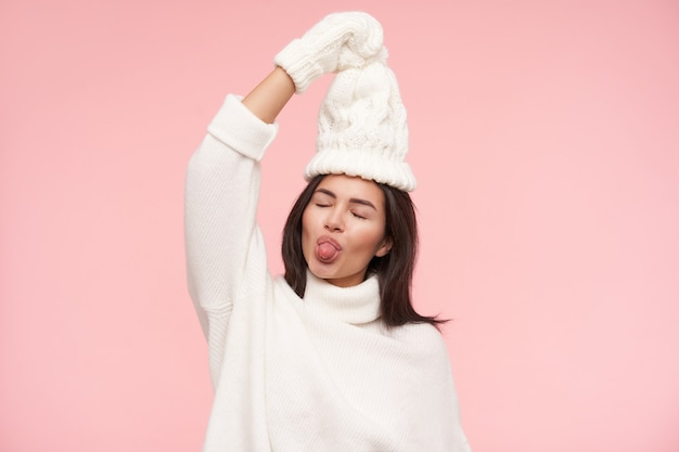 Pleasant looking young lovely sticking out her tongue with closed eyes while having fun, keeping raised hand above her head while standing over pink wall