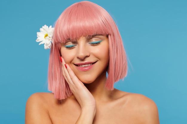 カモミールを髪につけて立って、目を閉じて前向きに笑いながら、頬に手のひらを持った色の化粧をした、心地よい若いピンクの髪の女性