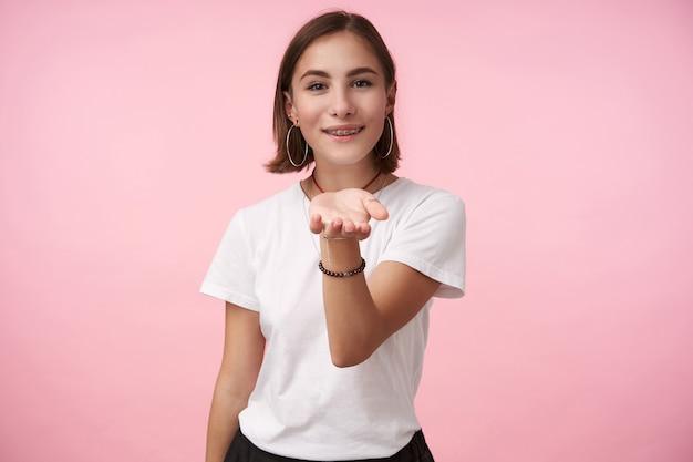 Приятно выглядящая молодая позитивная кареглазая брюнетка, слегка улыбаясь, поднимая ладонь, в простой белой футболке, позирует над розовой стеной