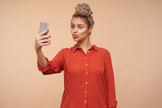 Pleasant looking young positive brown haired woman pursing her lips while making shot of herself on mobile phone, standing over beige wall in casual wear