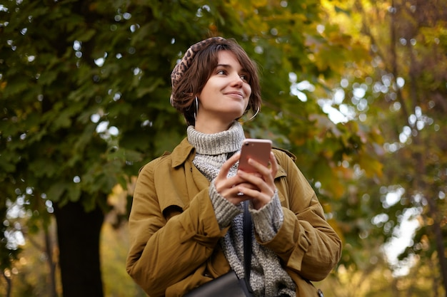 Pleasant looking young positive brunette female with bob hairstyle wearing stylish clothes while meeting her friends in city garen, keeping mobile phone in raised hands and smiling nicely