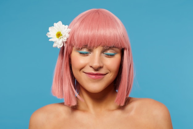그녀의 머리에 흰 꽃과 파란색 배경에 서, 진심으로 웃고있는 동안 눈을 감고 짧은 분홍색 머리를 가진 즐거운 찾고 젊은 긍정적 인 여자