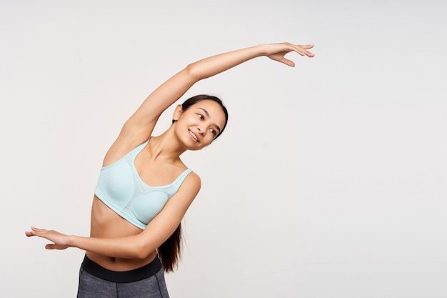 Pleasant looking young pretty brunette female without makeup being in nice mood while stretching her muscules in morning, isolated over white wall