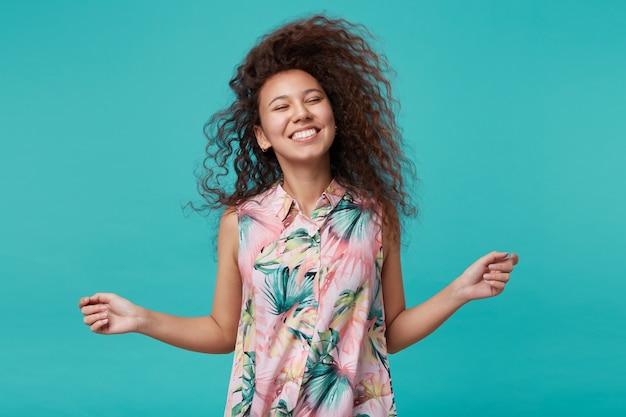 Giovane donna graziosa del brunette dall'aspetto piacevole che ondeggia i suoi lunghi capelli ricci e sorride felicemente con gli occhi chiusi, vestita in camicetta estiva mentre posa sull'azzurro