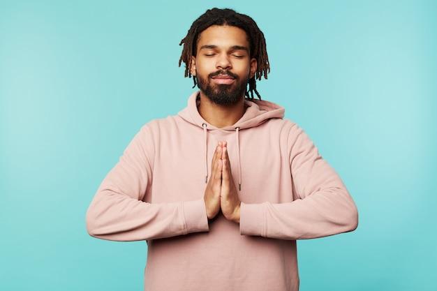 Piacevole dall'aspetto giovane uomo dalla pelle piuttosto scura che tiene gli occhi chiusi e piega i palmi sollevati insieme mentre si trova su sfondo blu in abbigliamento sportivo