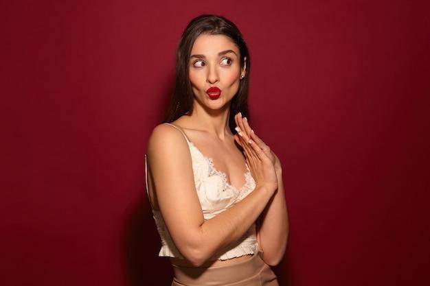赤い唇を持つ若いかなりうれしい長い髪のブルネットの女性を見て楽しい