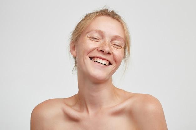 カジュアルな髪型で幸せそうに笑っている間目を閉じて、白い背景の上に立っている間彼女の目を閉じておく快適な赤毛の若い女性