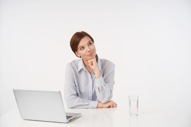 カジュアルな髪型の若い短い髪のブルネットの女性は、上げられた手で彼女のあごを傾け、前向きに笑って、白で隔離