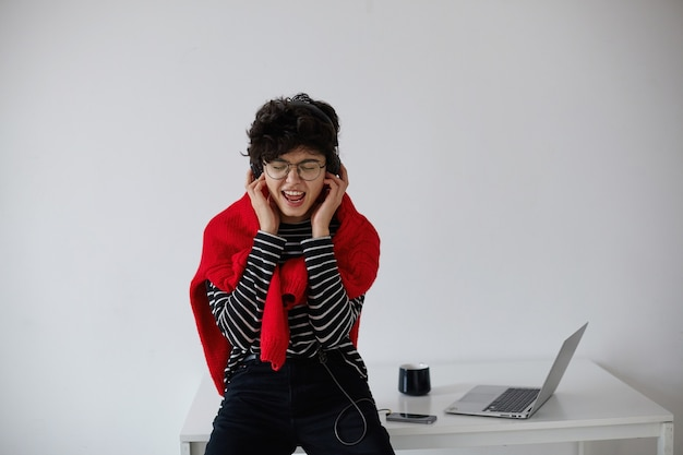 白い背景の上に座って、ヘッドフォンで音楽を聴き、歌いながら、ストライプのプルオーバーと赤いニットのセーターを着た眼鏡をかけた、見栄えの良い若い短い髪の巻き毛の女性