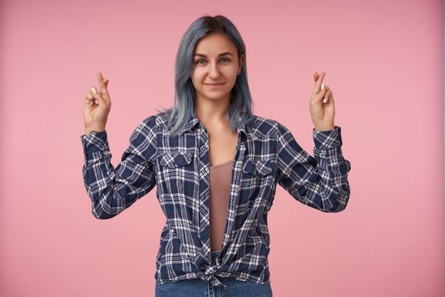 Piacevole giovane donna dai capelli corti con trucco naturale che tiene le dita incrociate e sorride dolcemente, indossa una camicia a scacchi sul rosa
