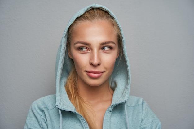 Giovane femmina bionda sorridente dall'aspetto piacevole con trucco naturale in posa su sfondo grigio chiaro, mantenendo le labbra piegate mentre indossa un cappotto di menta con cappuccio