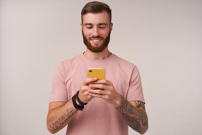 Приятно выглядящий молодой татуированный мужчина брюнетка с короткой стрижкой держит смартфон в поднятых руках и болтает со своими друзьями, стоя на белом с искренней улыбкой