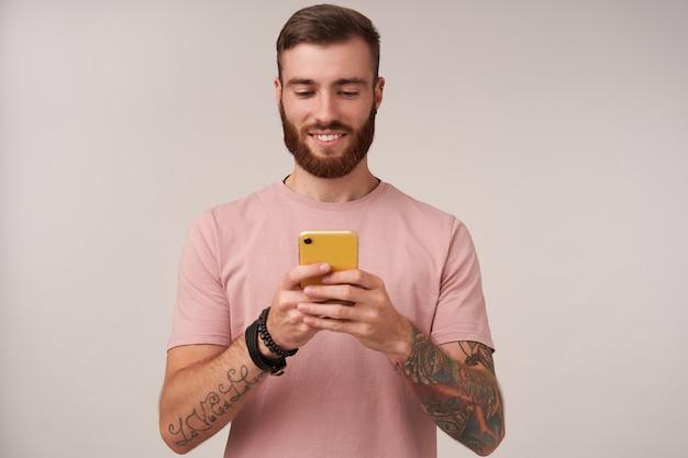 Giovane maschio brunetta tatuato dall'aspetto piacevole con taglio di capelli corto che tiene smartphone in mani alzate e chiacchiera con i suoi amici, in piedi su bianco con un sorriso sincero