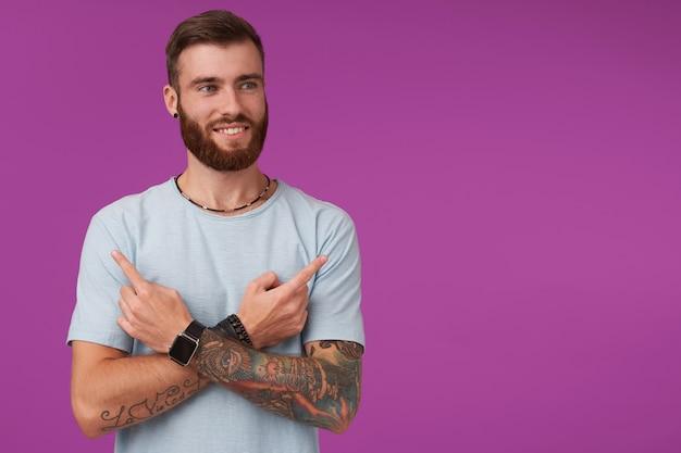 Giovane maschio tatuato dall'aspetto piacevole con la barba che sorride allegramente e indica con gli indici in diversi lati, indossa abiti casual mentre si trova sul viola