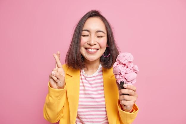 黒髪の東部の外観を持つ見栄えの良い若い女性は、アイスクリームを保持し、心地よい味を楽しんで指を交差させ、ピンクの壁に隔離されたファッショナブルな服を着て願い事をします