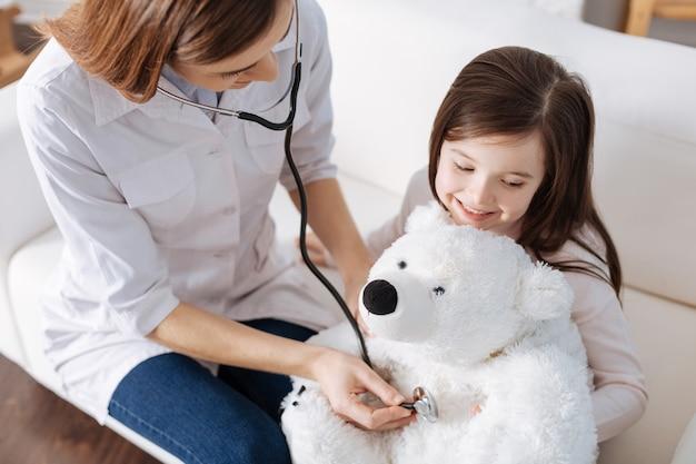 医者のふりをしながら娘の聴診器ぬいぐるみで調べてくれる愛情深いお母さん