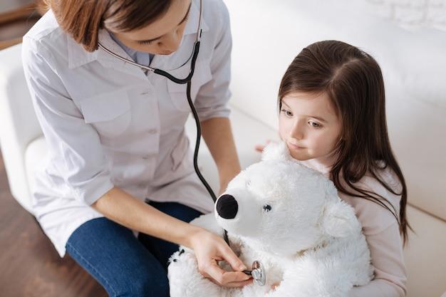 医者のふりをして娘のふわふわおもちゃを調べる気持ちのいい愛情深いお母さん