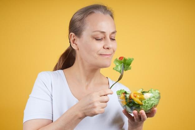 야채 샐러드를 먹는 흰 셔츠에 즐거운 성숙한여 인