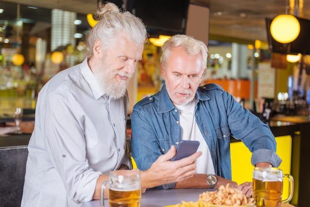 즐거운 만남. 스마트 폰 화면을 보면서 테이블에 함께 서있는 즐거운 긍정적 인 남자