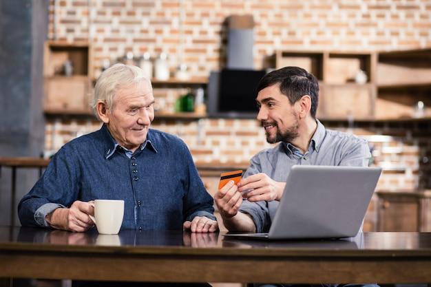 Приятный мужчина держит кредитную карту, показывая отцу банковские услуги