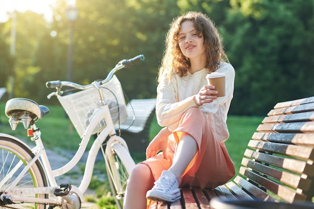 Pleasant moments. pretty young girl having coffee in the park in the morning