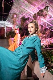 楽しい気分。写真を撮りながら青いドレスを着た魅力的な素敵な女性