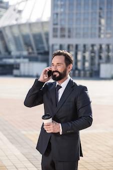 楽しい朝の話。電話で話している間コーヒーを飲む陽気なひげを生やしたビジネスマン
