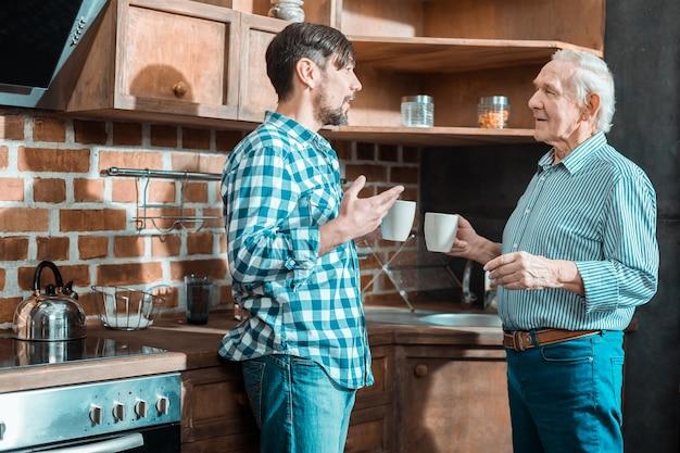 彼の父を見て、台所で彼と一緒に立っている間話している楽しい素敵なブルネットの男
