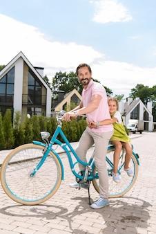 자전거의 뒤쪽에 앉아있는 동안 그녀의 아버지를 포옹하는 즐거운 좋은 여자