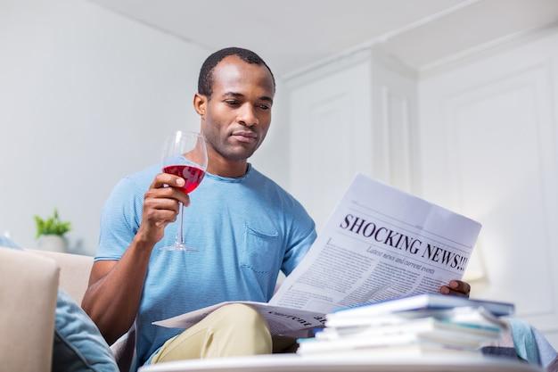 Приятный приятный красавец пьет вино и читает газету, отдыхая дома