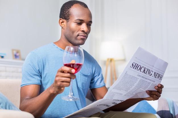 뉴스를 읽고 술을 마시는 동안 와인 한 잔을 들고 즐거운 좋은 잘 생긴 남자