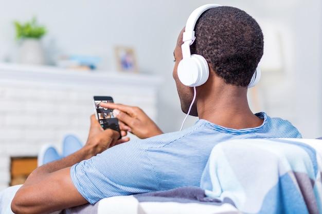 Приятный симпатичный красавец в наушниках и держит смартфон, выбирая песню