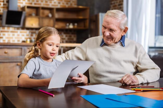 祖父と一緒にテーブルに座って紙を切る楽しい素敵な女の子