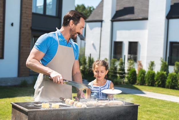 고기를 굽는 동안 그의 딸과 함께 서있는 즐거운 좋은 사람