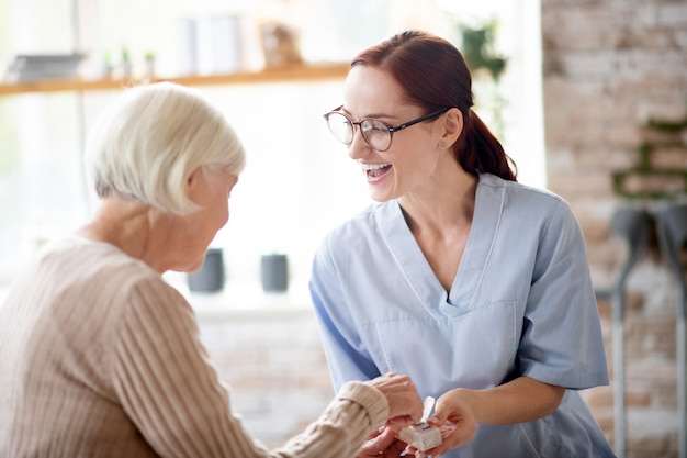 Pleasant nurse laughing while speaking with retired lady