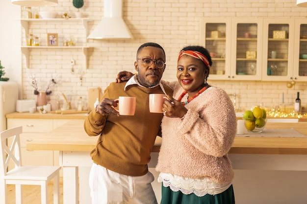 楽しい人たち。お茶と一緒に立っている間あなたを見ている肯定的なアフリカ系アメリカ人のカップル