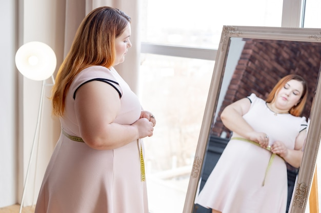 Приятная пухленькая женщина смотрит в зеркало, измеряя талию