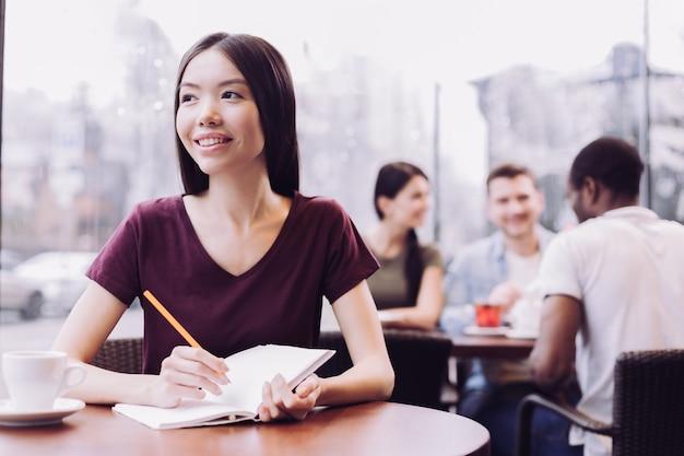 Приятная позитивная студентка держит карандаш и тетрадь, позируя в кафе и глядя в сторону