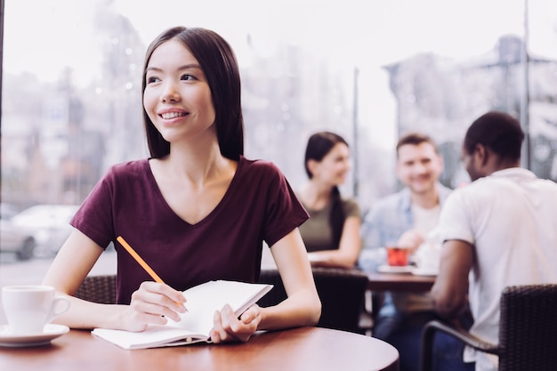 Pleasant positive female student holding pencil and notebook while posing at cafe and staring aside
