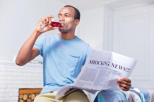 잔을 들고 신문을 읽는 동안 레드 와인을 마시는 즐거운 긍정적 인 잘 생긴 남자