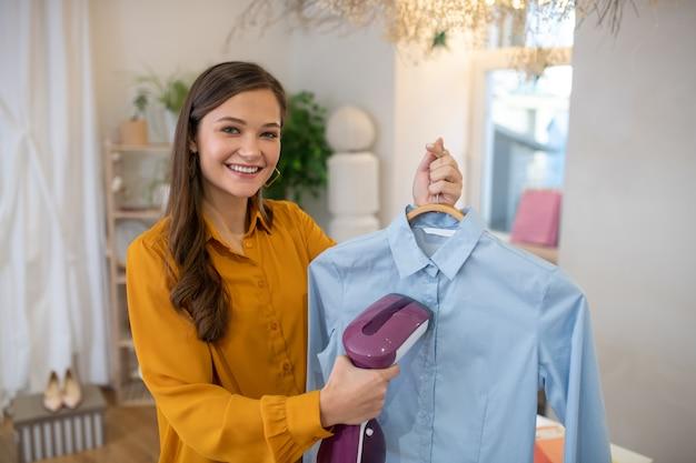 彼女のシャツにアイロンをかけている間蒸し器を保持している楽しいポジティブな女性